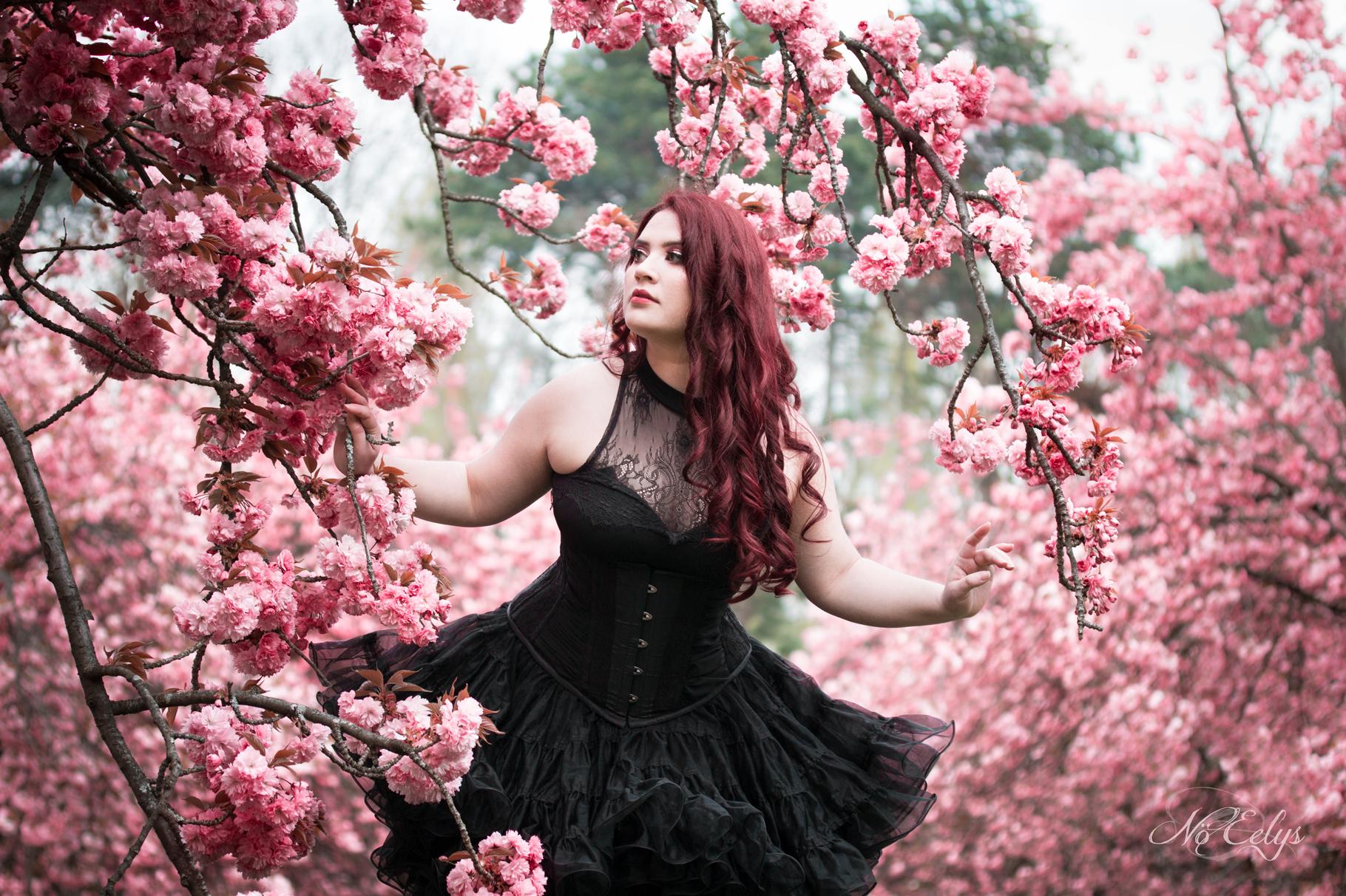 Portrait doux et romantique avec jupon et corset noirs et fleurs de cerisiers, modèle alternative Findelë's Secrets, photographe Nö Eelys, maquillage par Le Boudoir de Nö